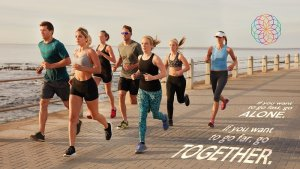Portrait of young people running along the beach boardwalk by the ocean. Fit young men and women running training outdoors by the seaside.